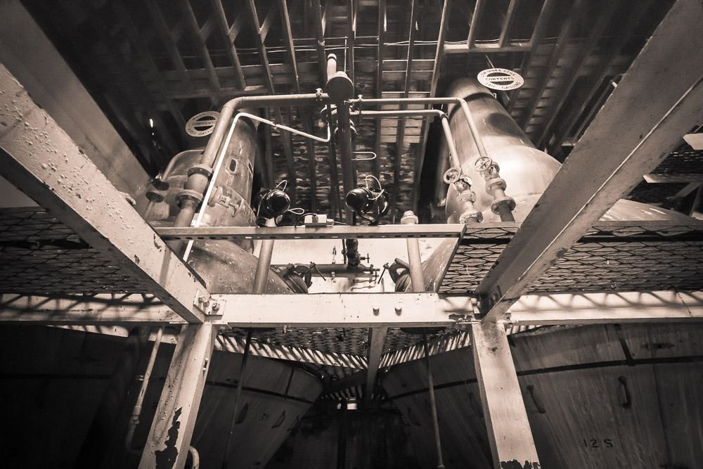 Black and white photo of Clynelish Brora spirit still and wash still and steel beam scaffold supports