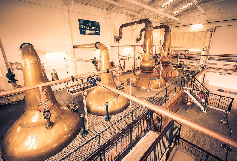 Wide angle copper tinted photo of Talisker Distillery spirit and wash stills