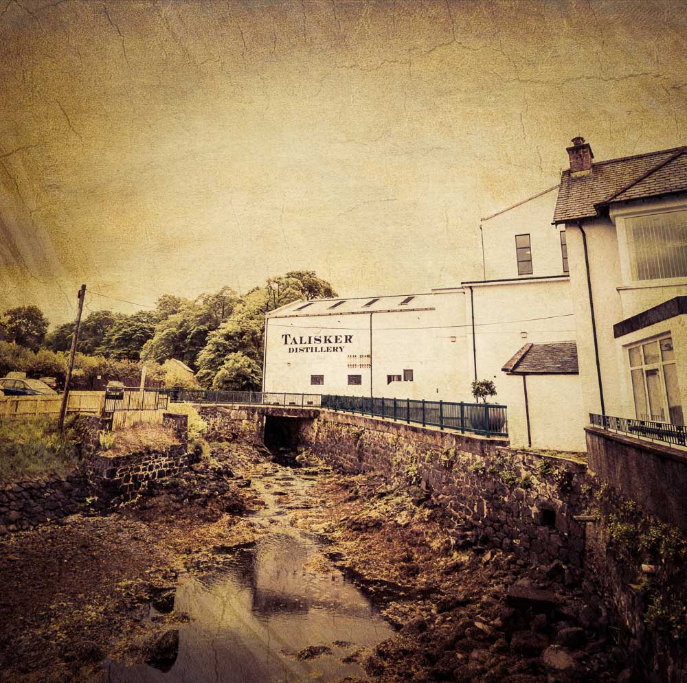 Talisker distillery building with a cracked sky effect and overlay of vintage paper