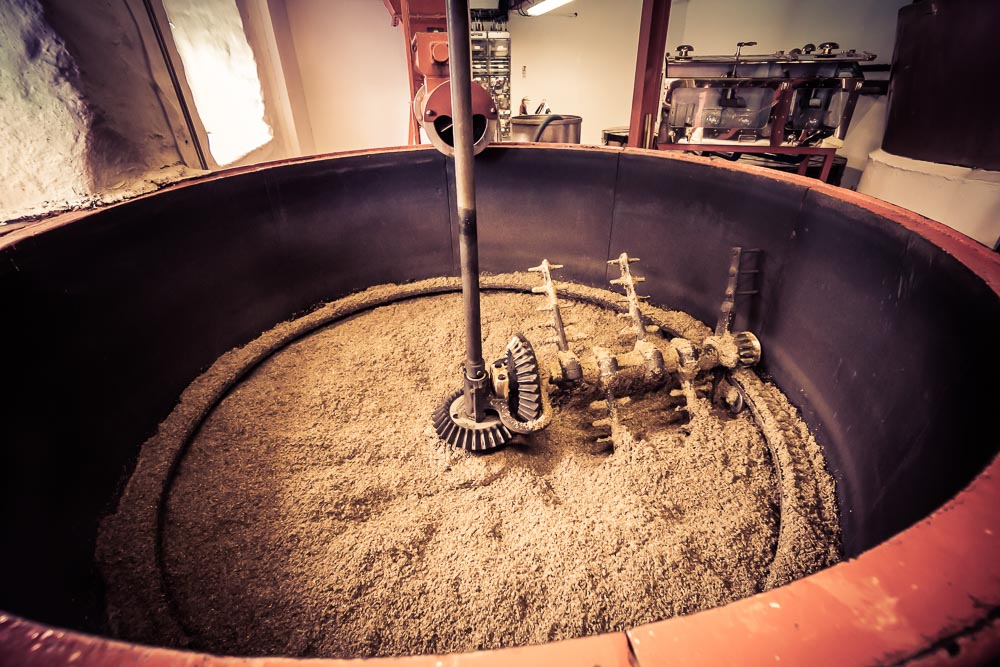 Edradour Mash Tun: 1.15 metric tonnes of malted barley is milled into grist daily, then added to 5500 litres of water at 69 deg C in the Mash Tun. The first mash cycle takes almost 2 hours, whereas the second cycle is 30 minutes shorter, using 1800 litres at 76 deg C. The strained liquids (Wort) from both the first and second cycles drain into the Underbacks. A third wash is then run at 87 deg C. The filtered Wort from this cycle gets transferred into a separate storage tank for reuse as the next 'first wash', rather than into the Underbacks. The third Wash/Wort has the least amount of sugar in it. By re-using it as the first wash for the next batch, it optimises the few sugars it does contain.