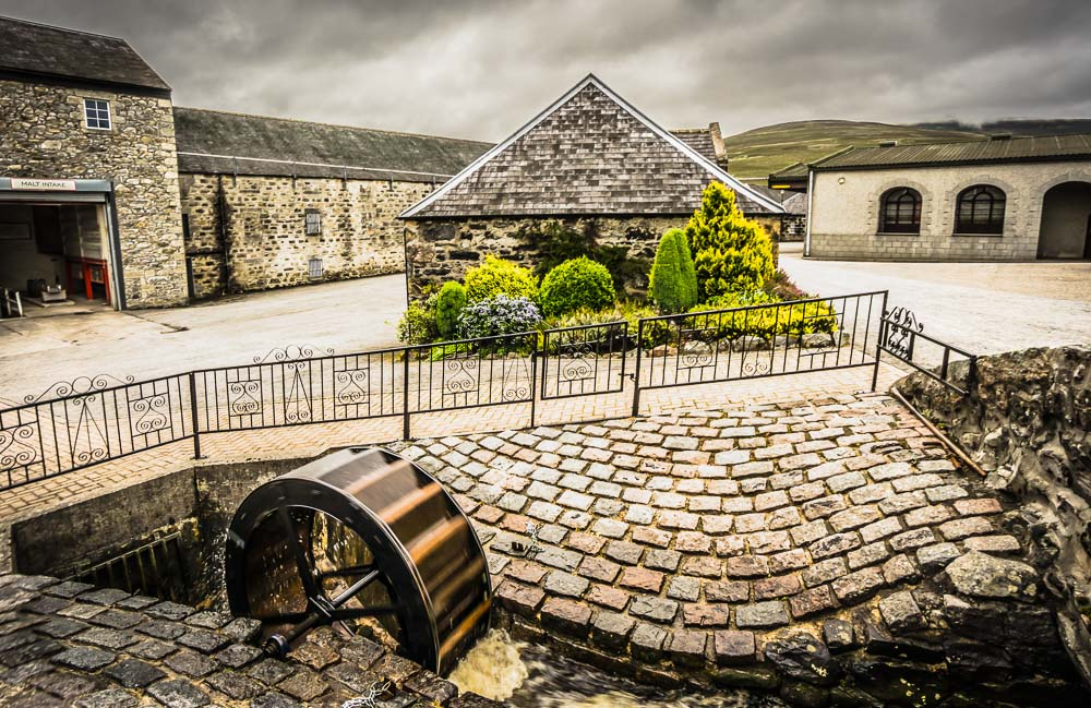 Glenfarclas Distillery courtyard, water wheel after much rain, and Benrinnes in the background.