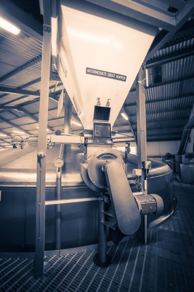 The intermediate grist hopper and steel lauter-style mash tun at Glenfarclas Distillery.