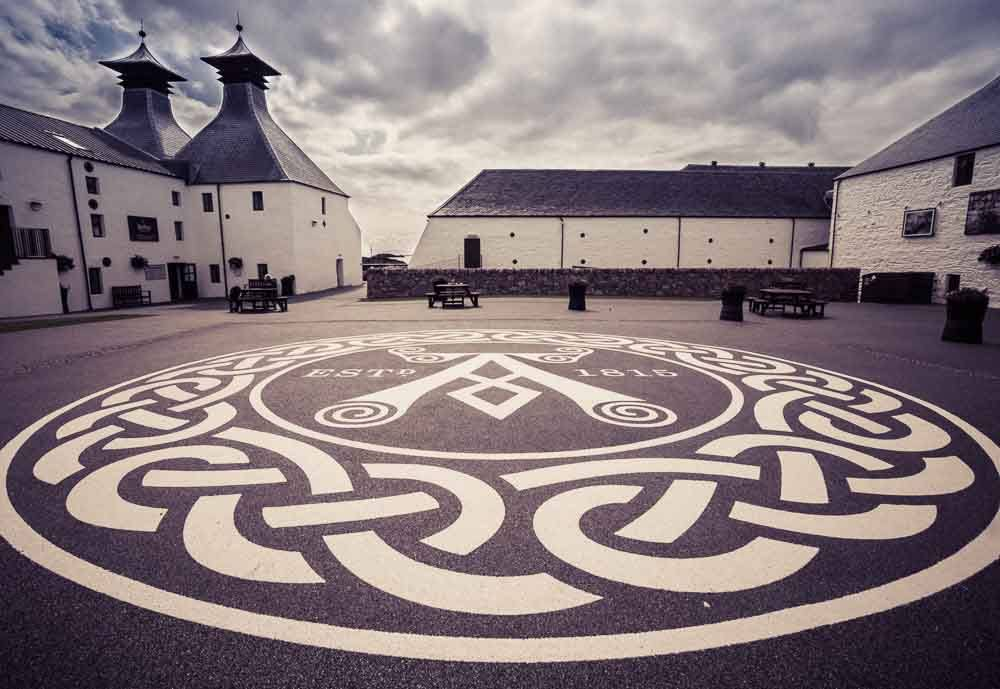 Purple toned photograph of the ​Main courtyard, Ardbeg Distillery, Islay, Scotland.