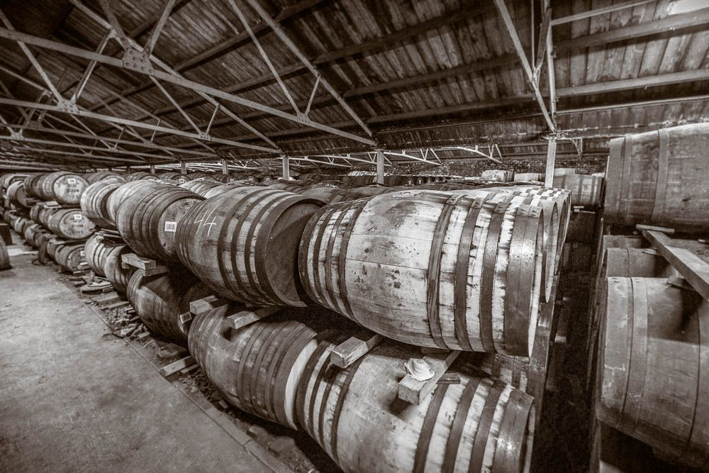 Black and white photo of racked casks in the warehouse at Ardbeg Distillery