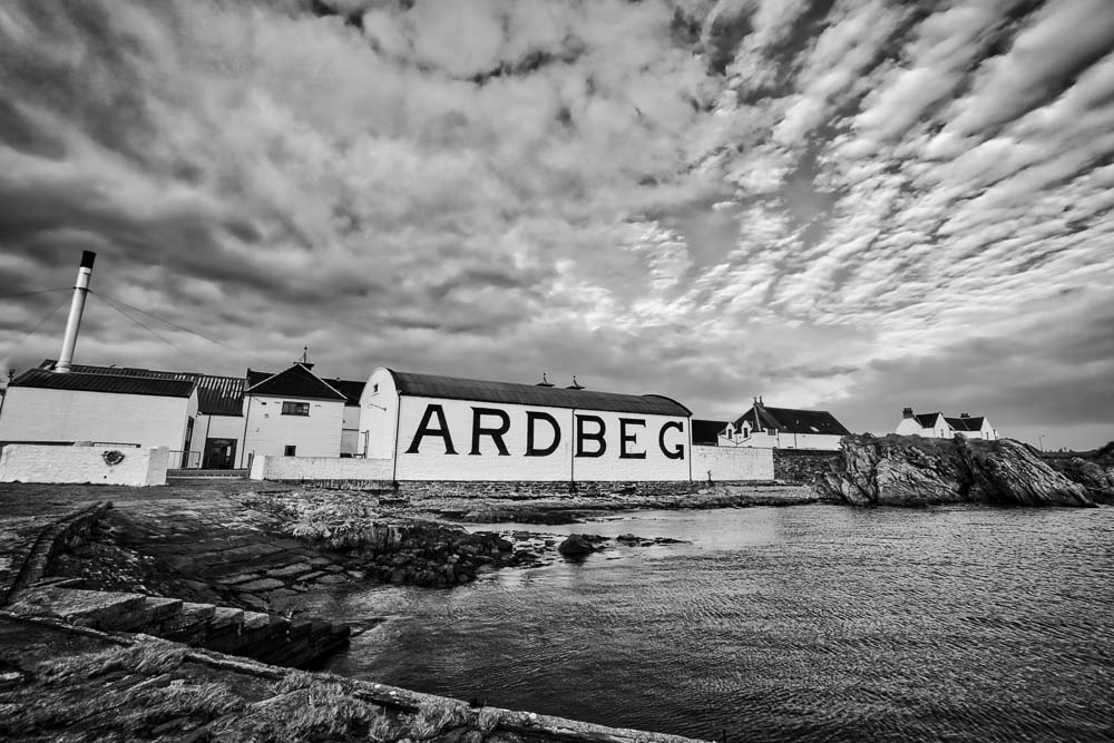 Black and white photograph of Ardbeg Whisky Distillery warehouse painted with Ardbeg name viewed from the pier