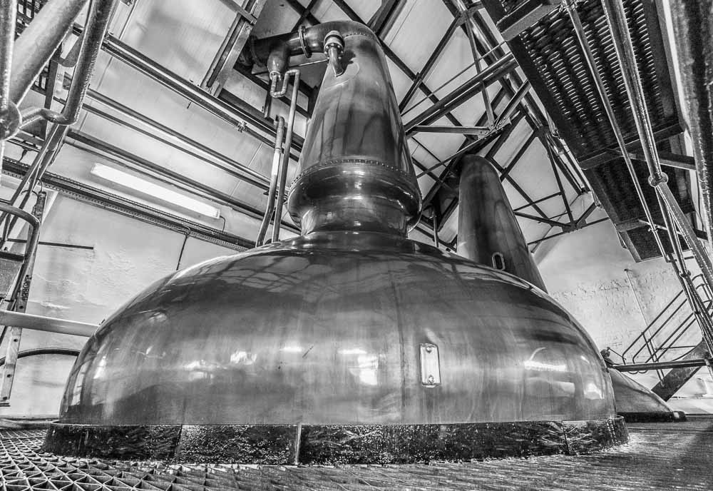 Wide angle view of the spirit still at Ardbeg Distillery, looking from the base, up to the neck and the lyne arm where the purifier (copper pipe leading from lyne arm back into the still) is also visible.