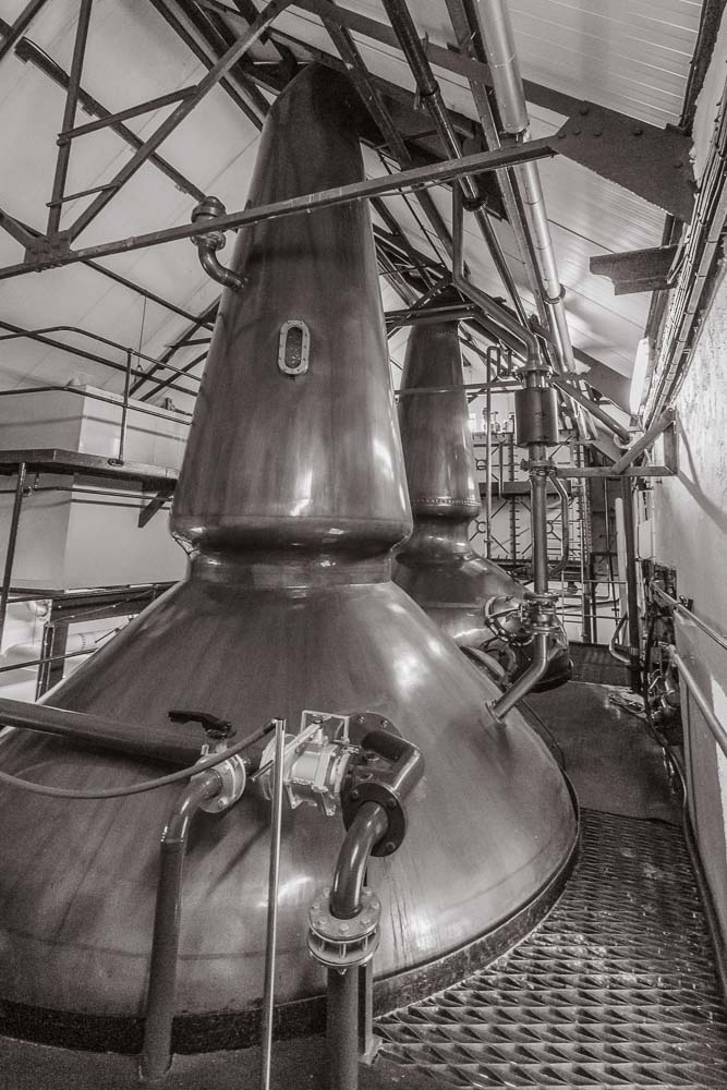 Black and white photo of the wash (front) and spirit (rear) stills at Ardbeg Distillery.