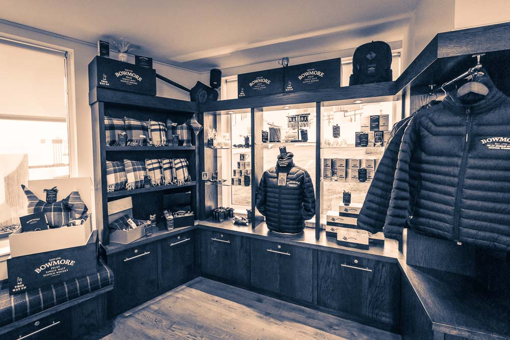 Merchandise including Bowmore Distillery jackets and scarves in the gift shop, inside the Bowmore Distillery visitor centre.