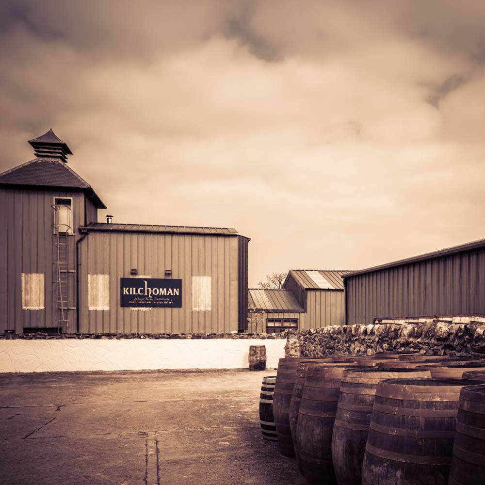 Soft colour photograph of Kilchoman Distillery Malt House and Kiln with Pagoda Stack, with casks awaiting filling in the right foreground.