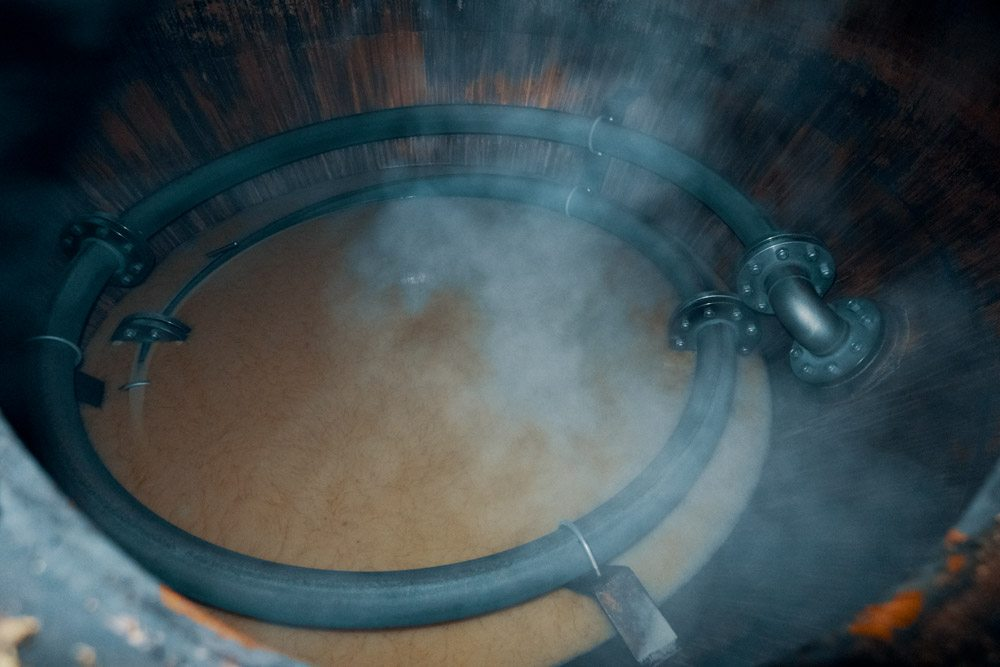 Steamy view inside the wash still at Kilchoman Distillery as the hot pot ale drains away