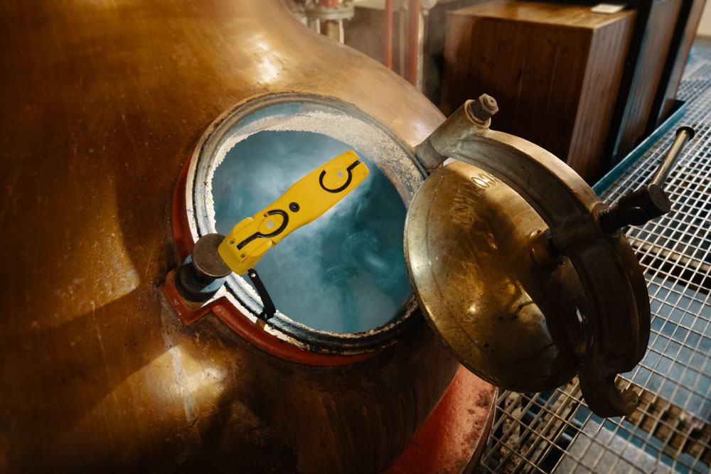 Open wash still steaming at Kilchoman Distillery, steam visible inside the still, colour photograph